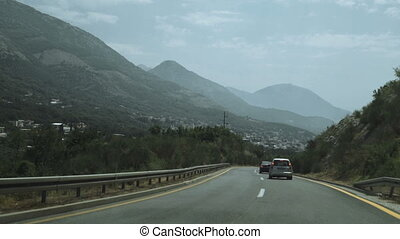Aerial shot of car passing on the highway to the mountains