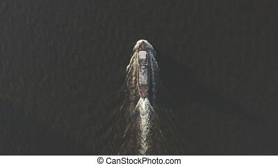 Aerial shot of cargo ship floats on the river or sea. Freight boat carriage goods. Drone fly over moves nautical vessel. Container ship or barge sailing. Transportation by maritime transport. Top view.