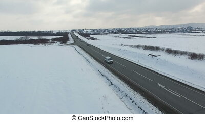 Aerial shot of cars and trucks driving on a road on winter cloudy day.