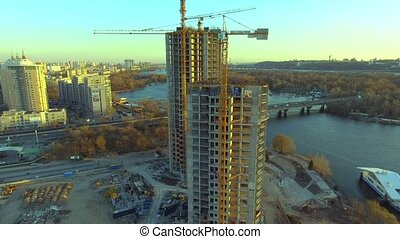 Aerial shot of construction site with cranes and workers at sunset.
