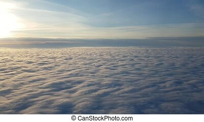Aerial shot of cottony clouds from a plane window at magic sunset in summer