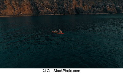 Aerial shot of couple kayaking in the sea during summer day....
