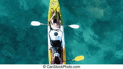 Aerial shot of couple kayaking in turquoise sea during summer day. Male operating drone remote
