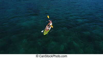 Aerial shot of couple kayaking in turquoise sea during summer day