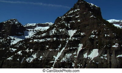 Aerial shot of craggy mountain peaks with melting snow