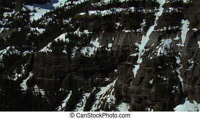 Aerial shot of craggy snow-covered mountain cliffs