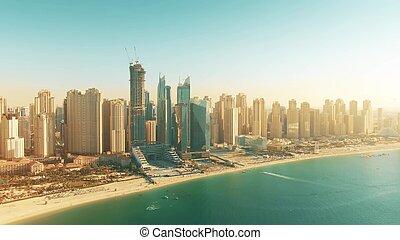 Aerial shot of Dubai Marina beach and skyscrapers on a sunny day, United Arab Emirates