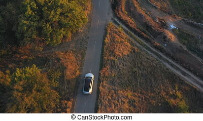 Aerial shot of electrical car driving through country road at summer evening. Modern vehicle passing rural highway. Ecology friendly car riding on electric charge along motorway. Top view Slow motion.