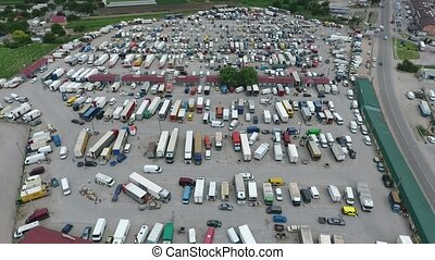Aerial shot of farmer`s market with kiosks, autos and trucks...