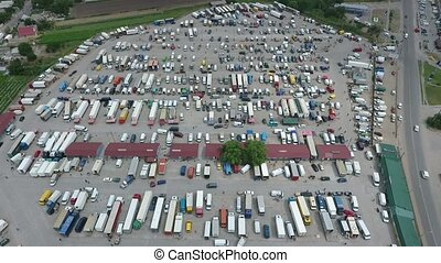 Aerial shot of farmer`s market with semi-trailer and double trucks in Ukraine