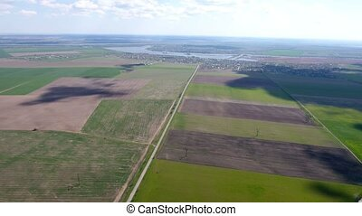 Aerial shot of fertile fields and country roads leading to a picturesque river