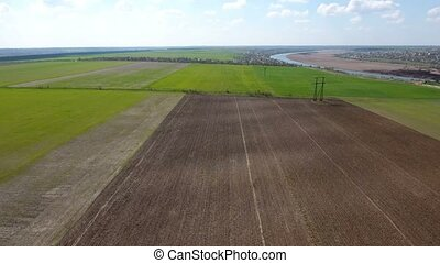 Aerial shot of fertile plowed field  leading to a river bank in a sunny day