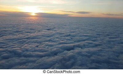 Aerial shot of fluffy clouds from a plane window at splendid sunset in summer