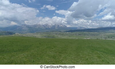 aerial shot of flying over a grassy field in a mountain valley