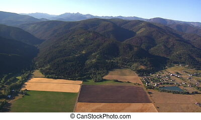 aerial shot of forest and mountainside and fields
