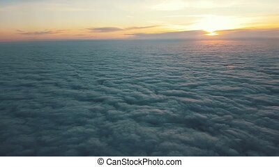Aerial shot of fuzzy clouds from a plane window at arty...