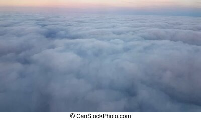 Aerial shot of fuzzy clouds with a violet horizon from a...