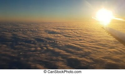 Aerial shot of golden and blue clouds from plane window at sunset in summer