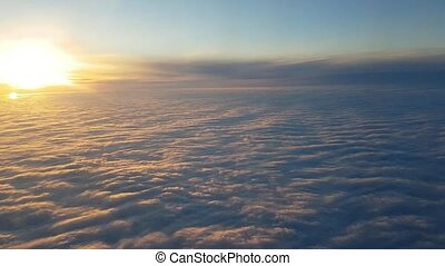 Aerial shot of golden and violet clouds seen from airplane at splendid sunset