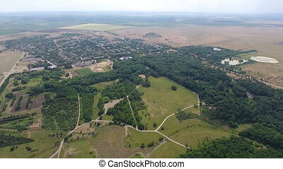Aerial shot of green lawns with counrty roads and wood areas on a sunny day,