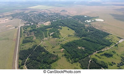 Aerial shot of green patches of forest between huge agricultural fields