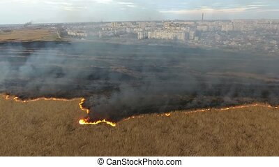 Aerial shot of grey smoke flows rising from burning Dnipro...