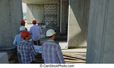 Aerial Shot Of Group Of Buiders Walking On Construction Site...