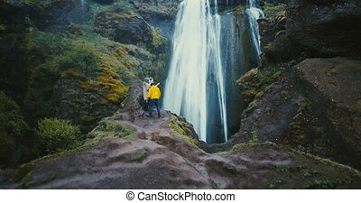 Aerial shot of group of tourists standing on top of cliff near the Gljufrabui waterfall in Iceland and enjoying the view