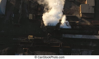 Aerial shot of heavy smoke pouring from chemical factory into atmosphere. Drone flying above industrial plant emitting toxic vapor to nature. Ecology and environmental pollution problem. Top view.