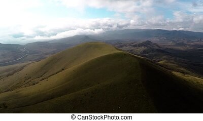 Aerial shot of hills and clouds at horizont. Shake from wind