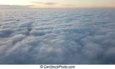 Aerial shot of hilly white clouds moving under a plane...
