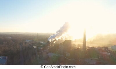 Aerial shot of industry zone pouring smoke from pipes into atmosphere. Drone flying above factory or plant emitting toxic vapor to air with sunlight at background. Nature pollution problem. Top view.