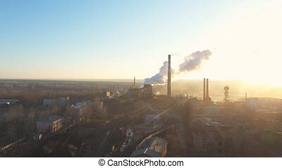 Aerial shot of industry zone pouring smoke from pipes into atmosphere. Drone flying above factory or plant emitting toxic vapor to air with sunlight at background. Environmental pollution problem.