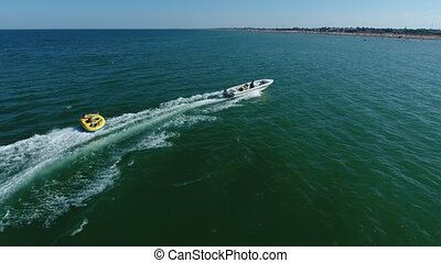 Hilarious view of a big white motorboat pulling inflatable ring with cheery people in shining sea on sunny day in summer. The ring makes snaky movements.
