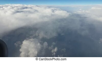 Aerial shot of large fluffy and white clouds from an aircraft window in summer