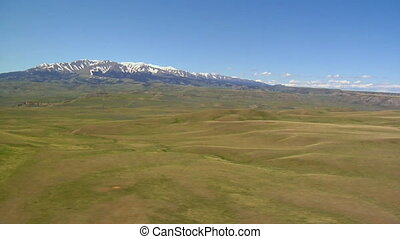 Aerial shot of lush green hills and meadows, blue-sky day