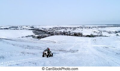 Aerial shot of man driving ATV at winter field - Man driving...