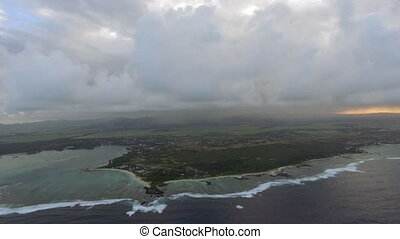 Aerial shot of Mauritius with low clouds and blue lagoons