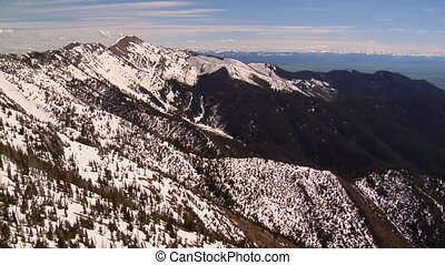 Aerial shot of melting snowy mountains, distant blue sky