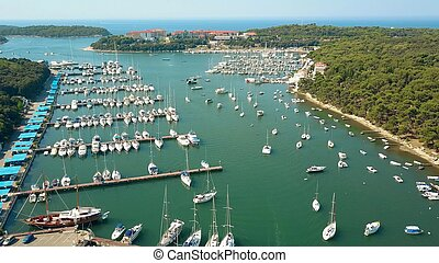 Aerial shot of multiple parked boats, motorboats and sailboats at the Adriatic sea marina