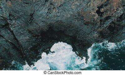 Aerial shot of ocean waves crashing coastline cliff
