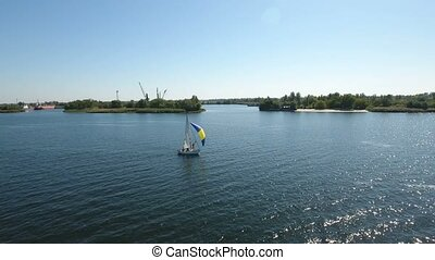 Aerial shot of one mast yacht with a blue and yellow sail floating in the Dnipro
