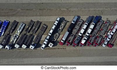 Aerial shot of parked car transporter trucks and trailers, top view. 4K video