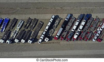 Aerial shot of parked car transporter trucks and trailers, top view