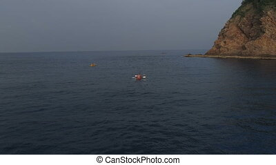 Aerial shot of people kayaking in the sea during summer day....