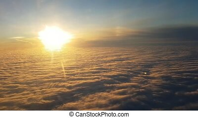 Aerial shot of picturesque clouds from soaring aircraft at sunset in summer