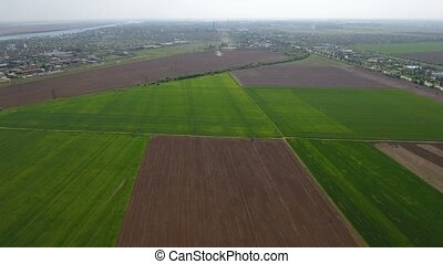 Aerial shot of plowed and green filelds not far from the Dnipro river
