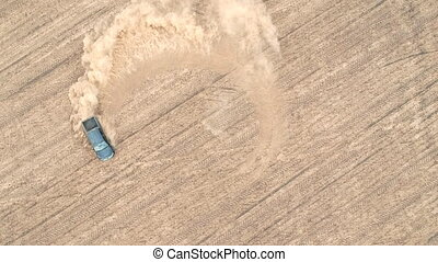 Aerial shot of powerful pickup drifting on dry ground. Black off road vehicle showing performance leaving trace and dust behind. SUV fastly starting ride at the field. Car drive at meadow. Top view.