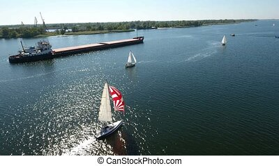 Aerial shot of regatta yachts bypassing a long barge in the Dnipro on a sunny day