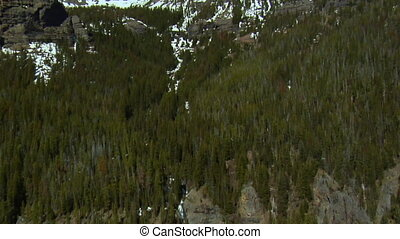 Aerial shot of rocky mountain peaks covered in melting snow